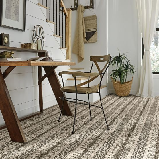 striped grey toned synthetic carpet with wood desk and chair