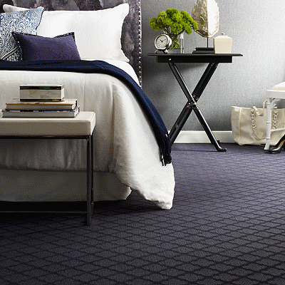 bed on dark grey wool carpet